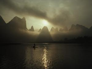 A Man in a Small Boat in Morning Mist Shrouding Karst Hills by James P. Blair