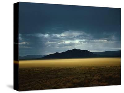 The Setting Sun Permeates Rain Clouds to Brighten Black Rock Desert, Nevada
