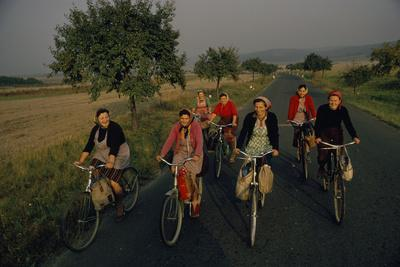 Women ride bicycles home from the fields in the Little Carpathians.
