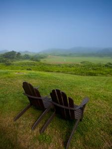 Adirondack Chairs on Lawn at Martha's Vineyard with Fog over Trees in the Distant View by James Shive