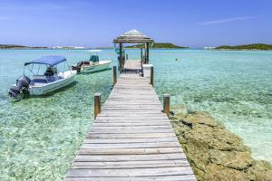 A Wood Pier Leads to Moored Boats and Clear Tropical Waters Near Staniel Cay, Exuma, Bahamas by James White
