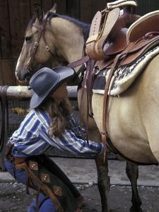 Female Wrangler Saddles Horse at Boulder River Ranch, Montana, USA by Jamie & Judy Wild