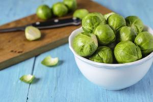 Fresh Brussels Sprouts in White Bowl on Turquoise Wooden Table by Jana Ihle