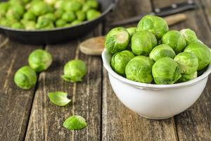 Fresh Brussels Sprouts in White Bowl on Wooden Table by Jana Ihle