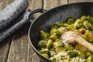 Pan-Fried Brussels Sprouts in Cast-Iron Frying Pan on Wooden Table by Jana Ihle