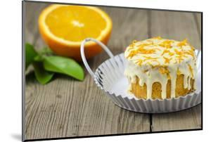 Small Orange Cake with White Icing on Wooden Table by Jana Ihle