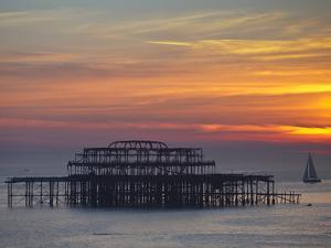 UK, England, Sussex, Brighton, Boat Sailing Past Remains of Brighton West Pier at Sunset by Jane Sweeney