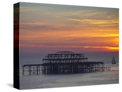 UK, England, Sussex, Brighton, Boat Sailing Past Remains of Brighton West Pier at Sunset