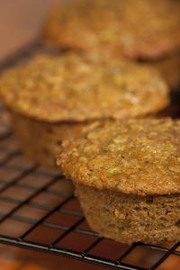Freshly baked zucchini muffins cooling on a wire rack by Janet Horton