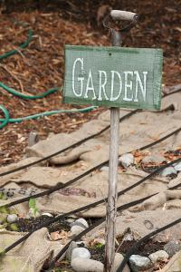 Issaquah, Washington State, USA. Garden sign and burlap bags covering dormant vegetable garden. by Janet Horton