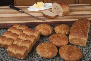 Multigrain rolls, buns and loaf with a slice cut off, with butter and a bread knife. by Janet Horton