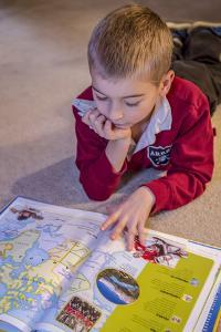 Seven year old boy reading his world atlas book. (MR) by Janet Horton