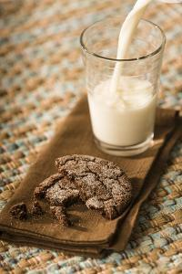 Snack of a homemade chocolate sugar cookie, with milk being poured into a glass. by Janet Horton