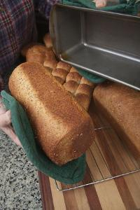 Woman removing loaf of just baked multigrain bread from bread pan. (MR) by Janet Horton