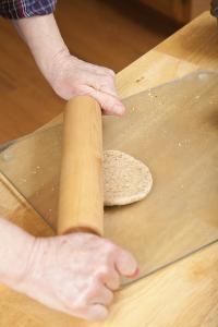 Woman rolling multigrain bread dough into circles to make hamburger buns. (MR) by Janet Horton