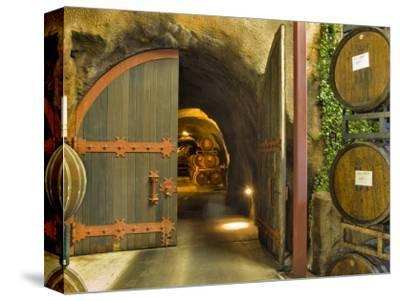 Oak Barrels Stacked Outside of Open Door To Aging Caves at Ironstone Winery, California, USA