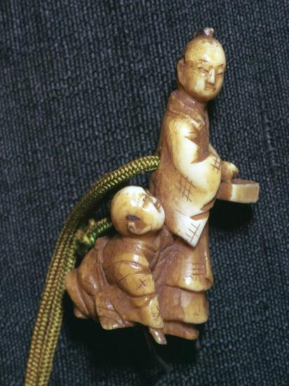 Japanese Netsuke of a man and boy at new year, 19th century. Artist: Unknown-Unknown-Giclee Print