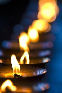 A Candle Flickers in a Brass Butter Lamp in the Prayer Room of an Ancient Buddhist Monastery by Jason Edwards