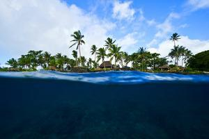 A Coral Reef Lines the Shore Beneath a Tropical Island Resort by Jason Edwards