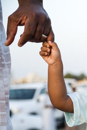 A Father Holds His Daughter's Hand on the Way to a Traditional Bull Fight by Jason Edwards