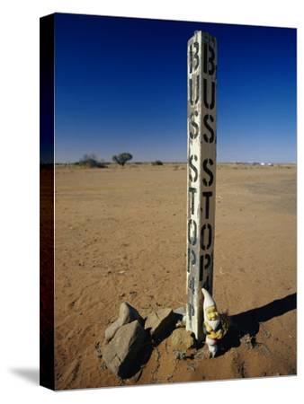 A Garden Gnome at a Bus Stop in an Outback Desert Town