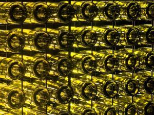Garden Wall Made of Recycled Glass Wine Bottles Illuminated at Night by Jason Edwards