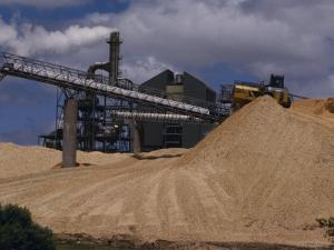 Logging Wood Chip Mill and a Tractor Atop a Vast Mound of Pulp, Australia by Jason Edwards