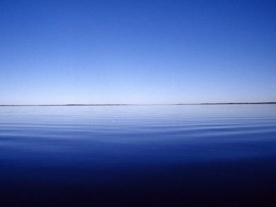 Mirror Calm Surface of a Rich Blue Coastal Lake on a Summers Day