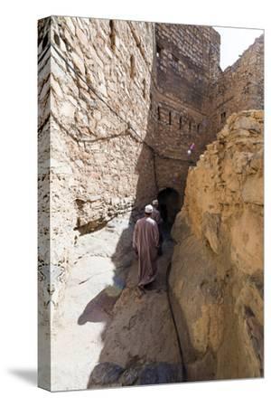 Muslim Men Walking Along a Narrow Mud Brick Alleyway in an Ancient Village in the Desert