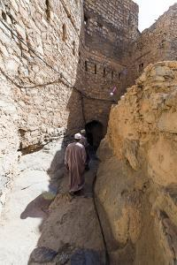 Muslim Men Walking Along a Narrow Mud Brick Alleyway in an Ancient Village in the Desert by Jason Edwards