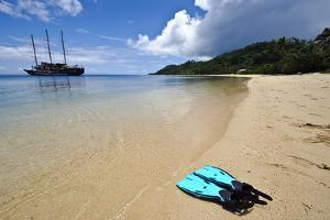 Snorkelers Fins on the Deserted Beach of a Pristine Tropical Island by Jason Edwards