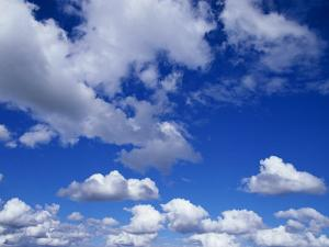 Sunlit Fluffy White Clouds in a Blue Sky by Jason Edwards