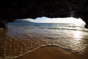 The Lip of a Foamy Wave Laps a Sandy Beach Inside an Ocean Cave by Jason Edwards