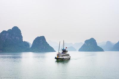 A boat passes through foggy karst landscape in Ha Long Bay, Quang Ninh Province, Vietnam, Indochina by Jason Langley