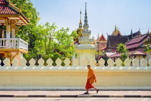 A buddhist monk walks past Wat Si Saket (Wat Sisaket) temple in central Vientiane, Laos by Jason Langley