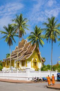 Monks passing Haw Pha Bang temple on the grounds of the Royal Palace, Luang Prabang, Louangphabang  by Jason Langley