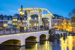 Netherlands, North Holland, Amsterdam. Magere Brug, Skinny Bridge, on the Amstel River at night. by Jason Langley