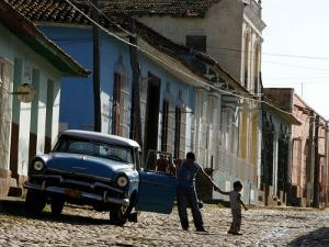 A Cuban Man Gets out of His Car with His Child by Javier Galeano