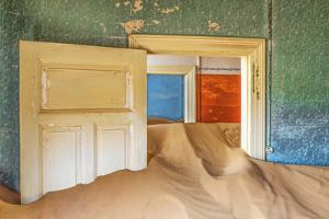 Africa, Namibia, Kolmanskop. Doorways and drifting sand in an abandoned diamond mining town. by Jaynes Gallery