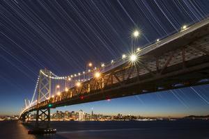 California, San Francisco. Composite of Star Trails Above Bay Bridge by Jaynes Gallery