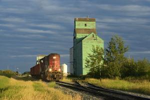Canada, Alberta, Sexsmith. Grain elevators and train on railroad tracks. by Jaynes Gallery