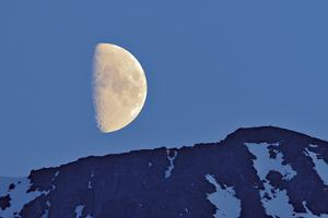 Canada, British Columbia. Half moon rising above mountain. by Jaynes Gallery