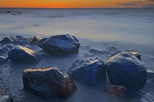 Canada, Manitoba, Winnipeg. Waves on shoreline rocks of Lake Winnipeg at dusk. by Jaynes Gallery