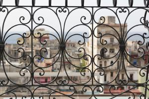 Cuba, Havana. Late afternoon rainbow and city viewed through wrought iron railing. by Jaynes Gallery