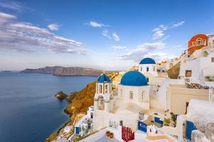 Greece, Oia. Greek Orthodox church and village. by Jaynes Gallery