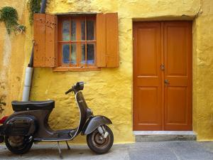 Greece, Rhodes. Vespa motorbike and colorful house exterior. by Jaynes Gallery
