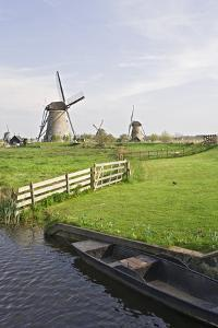 Netherlands, Kinderdijk. Windmills and boat next to canal. by Jaynes Gallery