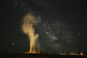 USA, Wyoming, Yellowstone NP. Milky Way and erupting Old Faithful Geyser. by Jaynes Gallery
