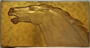 A fine golden lacquered and carved panel deeply carved in intaglio with the head of a stallion by Jean Dunand