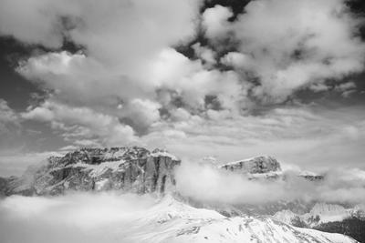 Clouds hang between the mountains of the Dolomites by Jean Schwarz